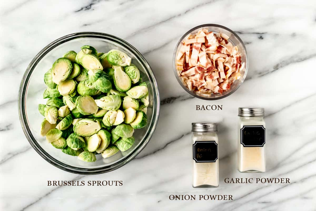 Ingredients needed to make brussels sprouts and bacon on a marble background with labels