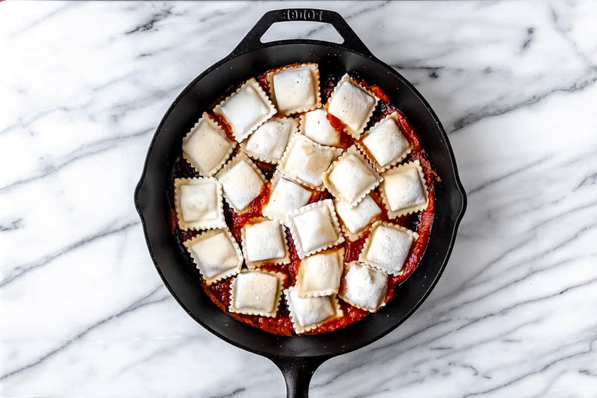 Frozen ravioli on top of sauce in a cast iron skillet