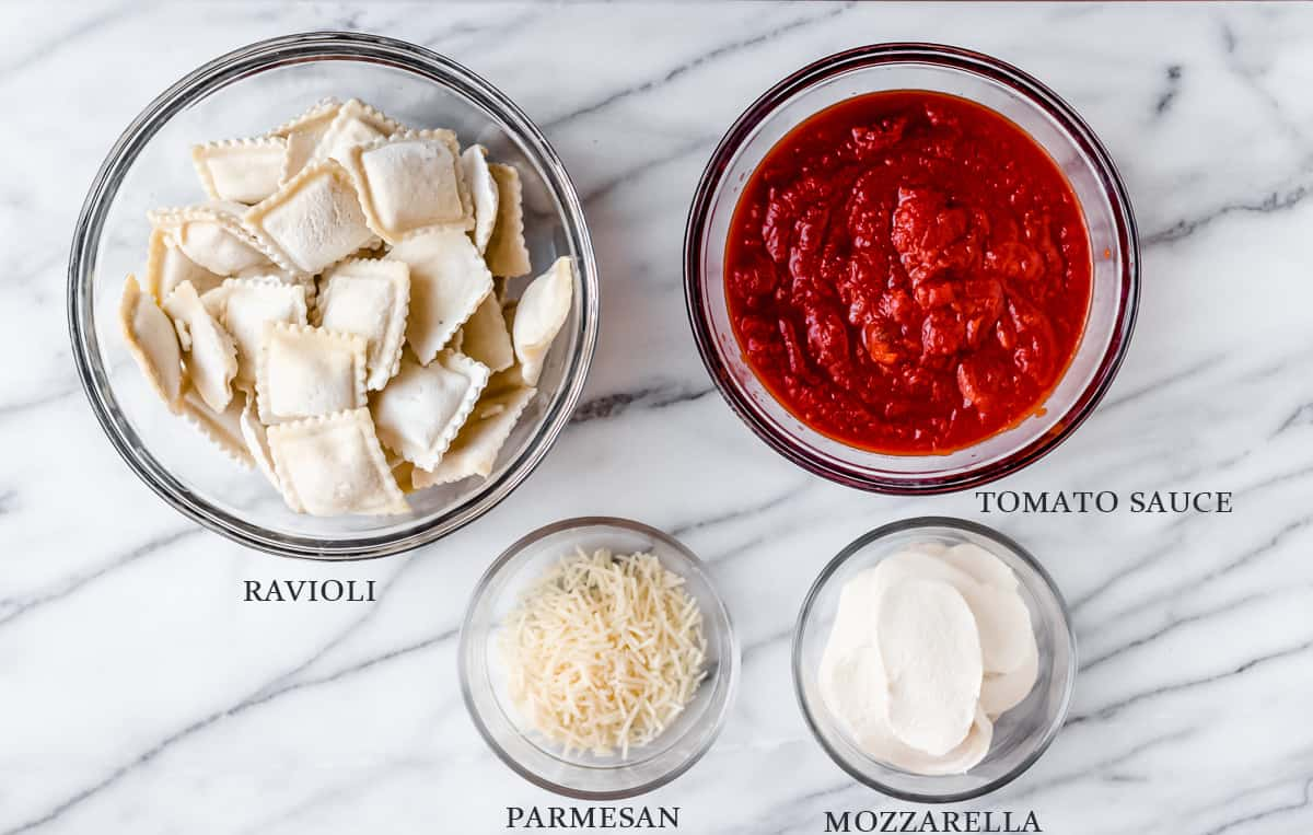 Ingredients needed to make a ravioli casserole on a marble background with labels