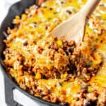 Close up of cheesy taco skillet being lifted up with a wood spoon