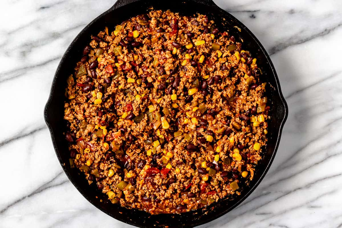 Seasoned turkey, corn, black beans, peppers and salsa in a cast iron skillet