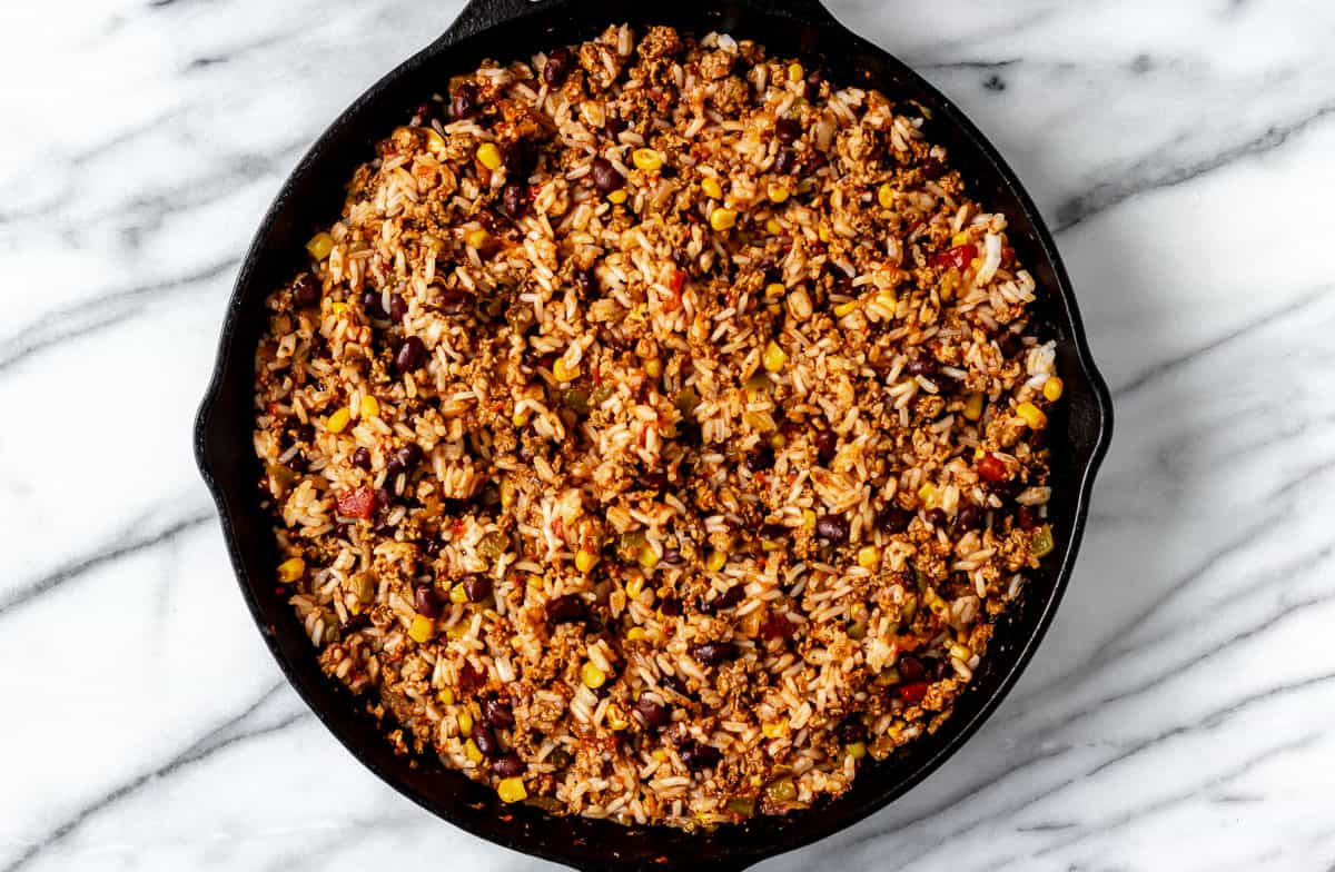 Seasoned turkey, rice, black beans, corn and salsa in a cast iron skillet