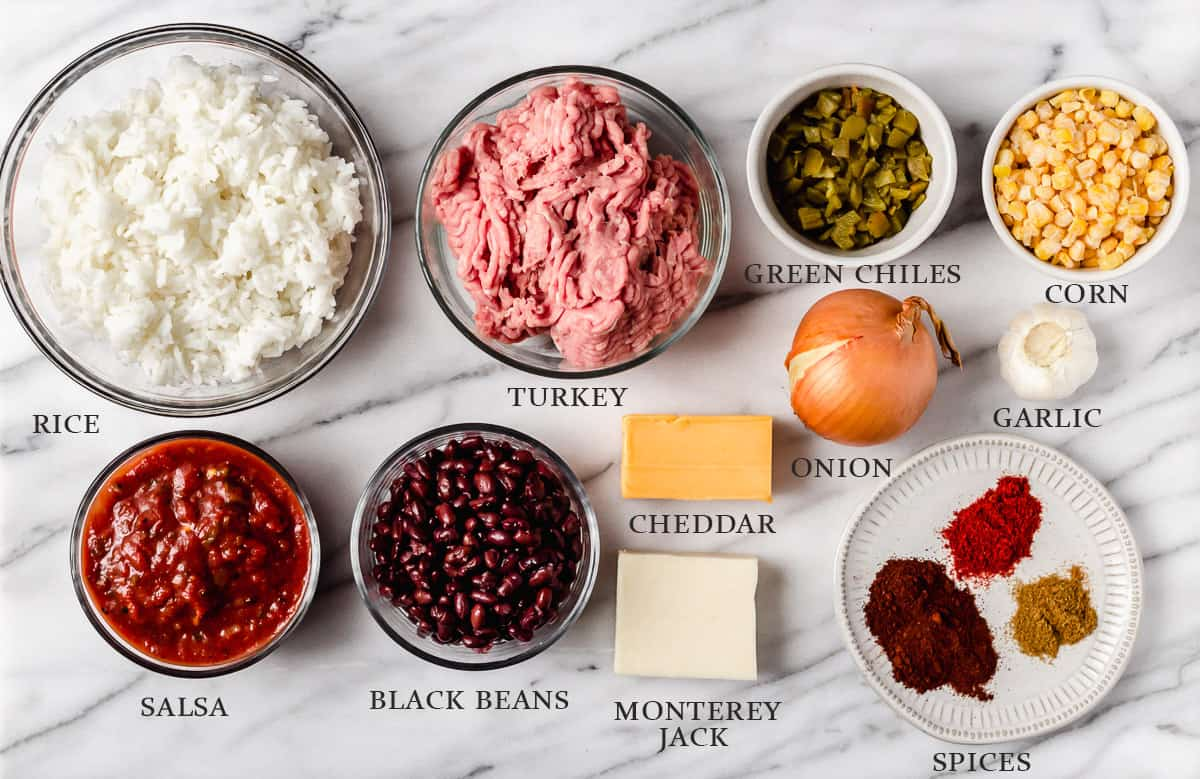 Ingredients needed to make a taco skillet on a marble background with labels