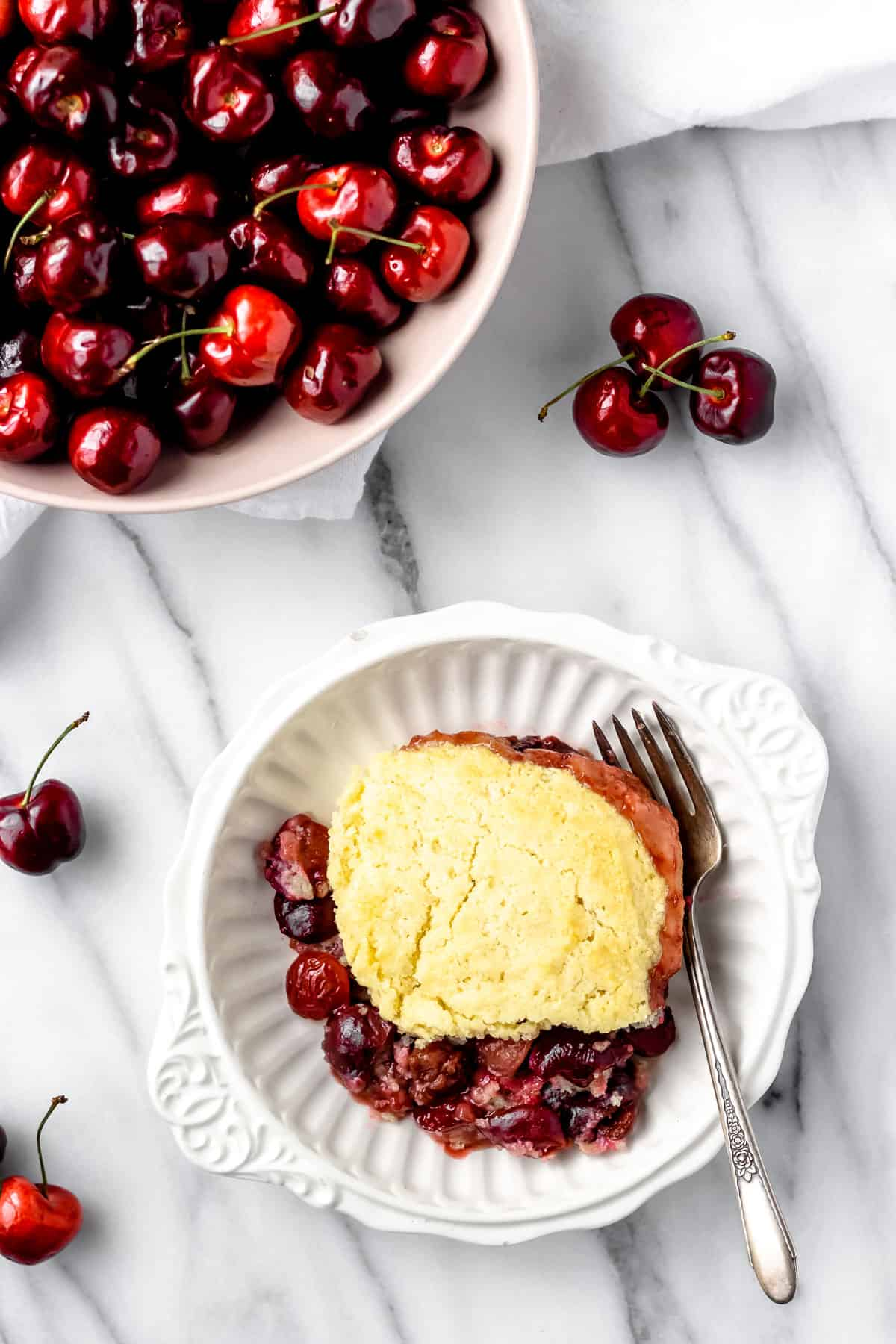 Overhead view of cherry cobbler in a white bowl with a bowl of cherries and several cherries scattered around