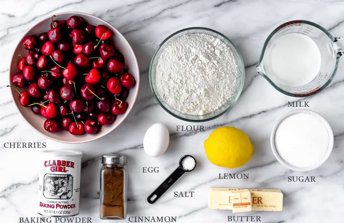 Ingredients to make cherry cobbler on a marble background with labels