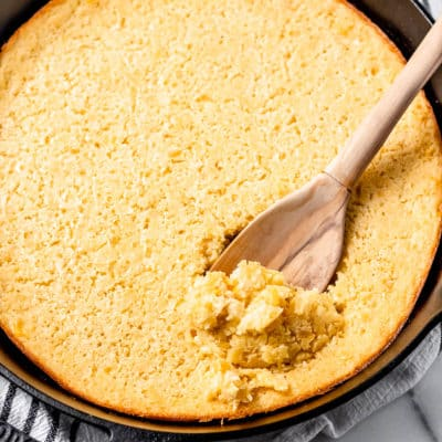 Corn souffle being scooped up with a wood spoon in a cast iron skillet
