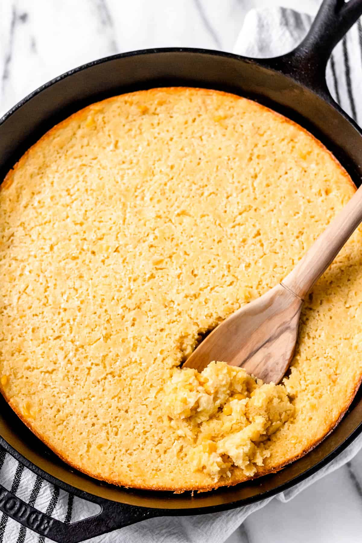 Corn soufflé being scooped up with a wood spoon in a cast iron skillet