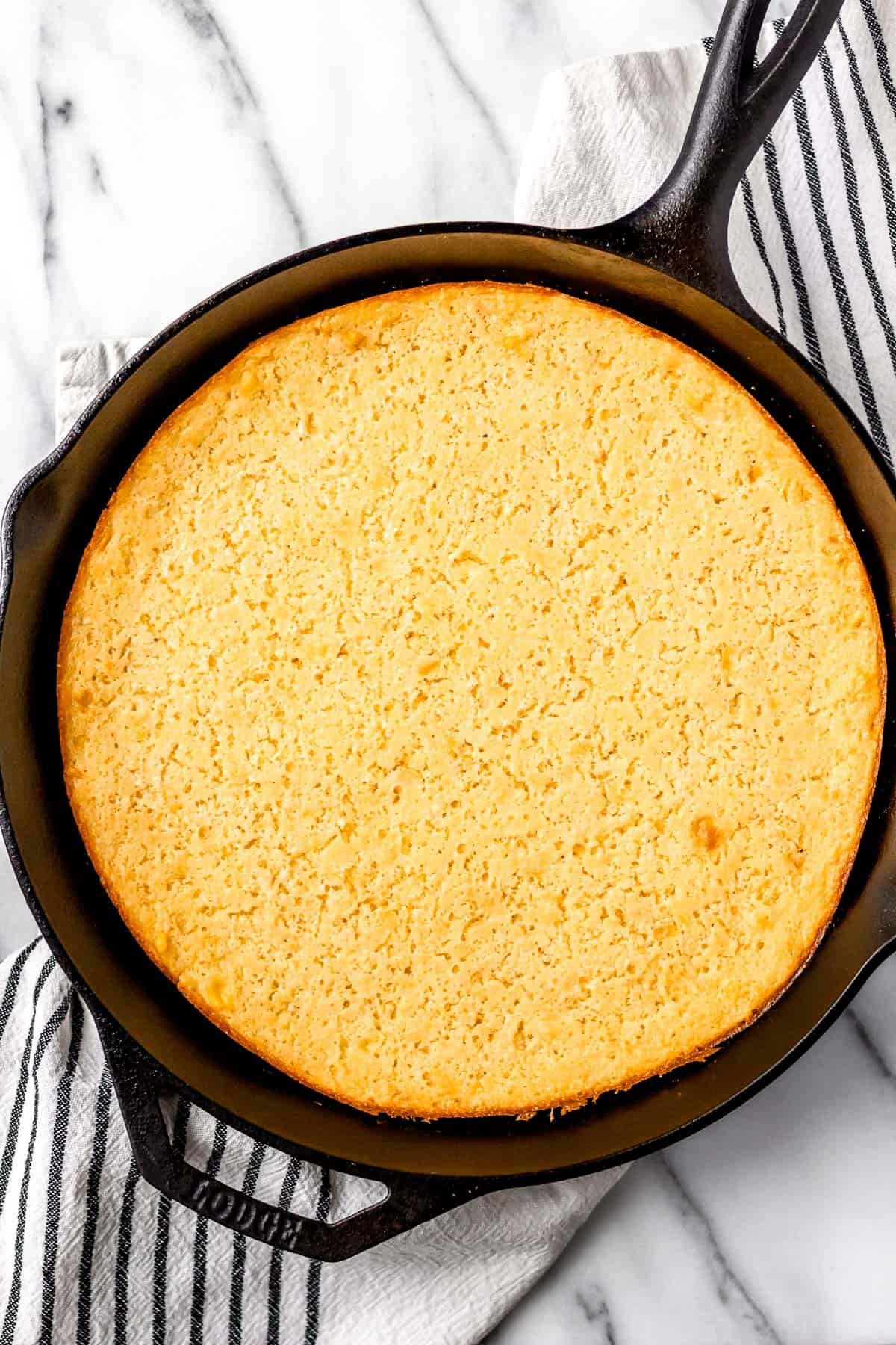 Corn souffle in a cast iron skillet over a cream and black towel on a marble background
