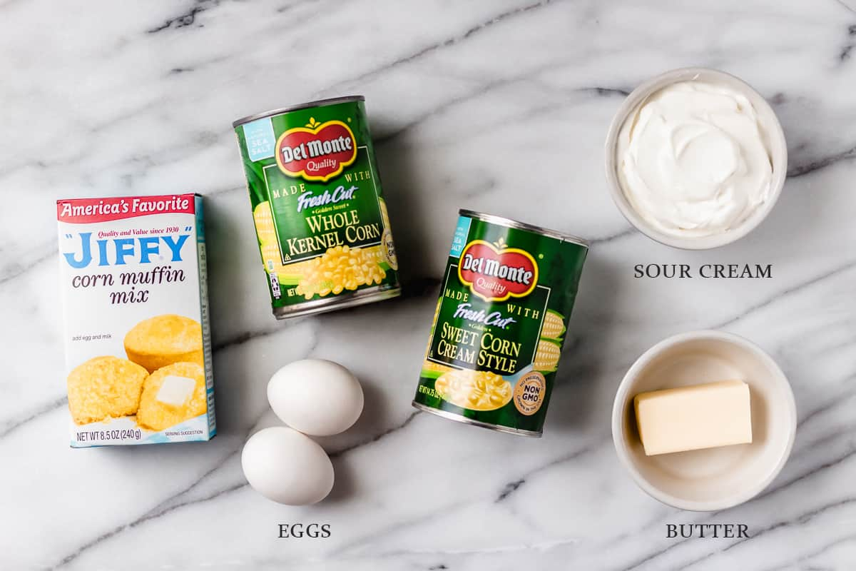 Ingredients needed to make corn soufflé on a marble background with labels