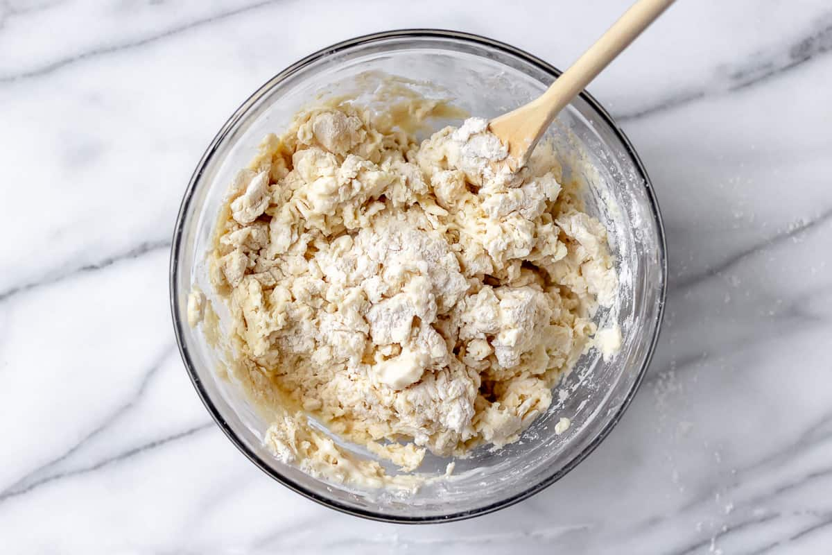 Biscuit dough in a glass bowl with a wood spoon on a marble backdrop