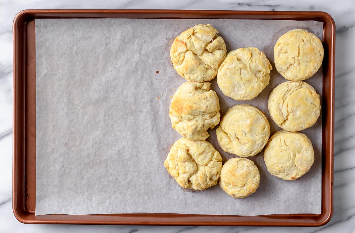 9 baked biscuits on a parchment paper lined baking sheet