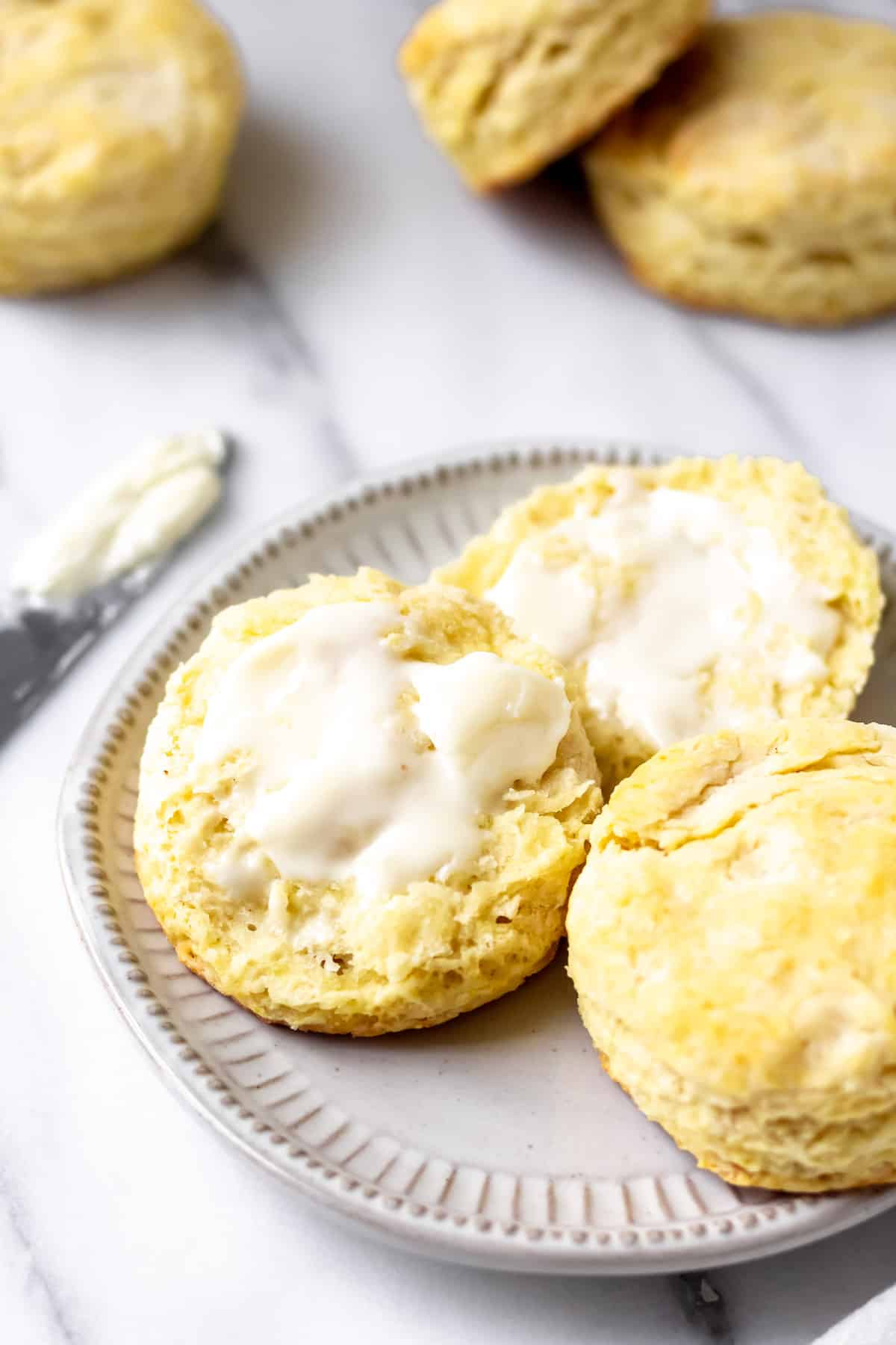 homemade country biscuits with one cut open and buttered on a plate with a second whole biscuit and more in the background