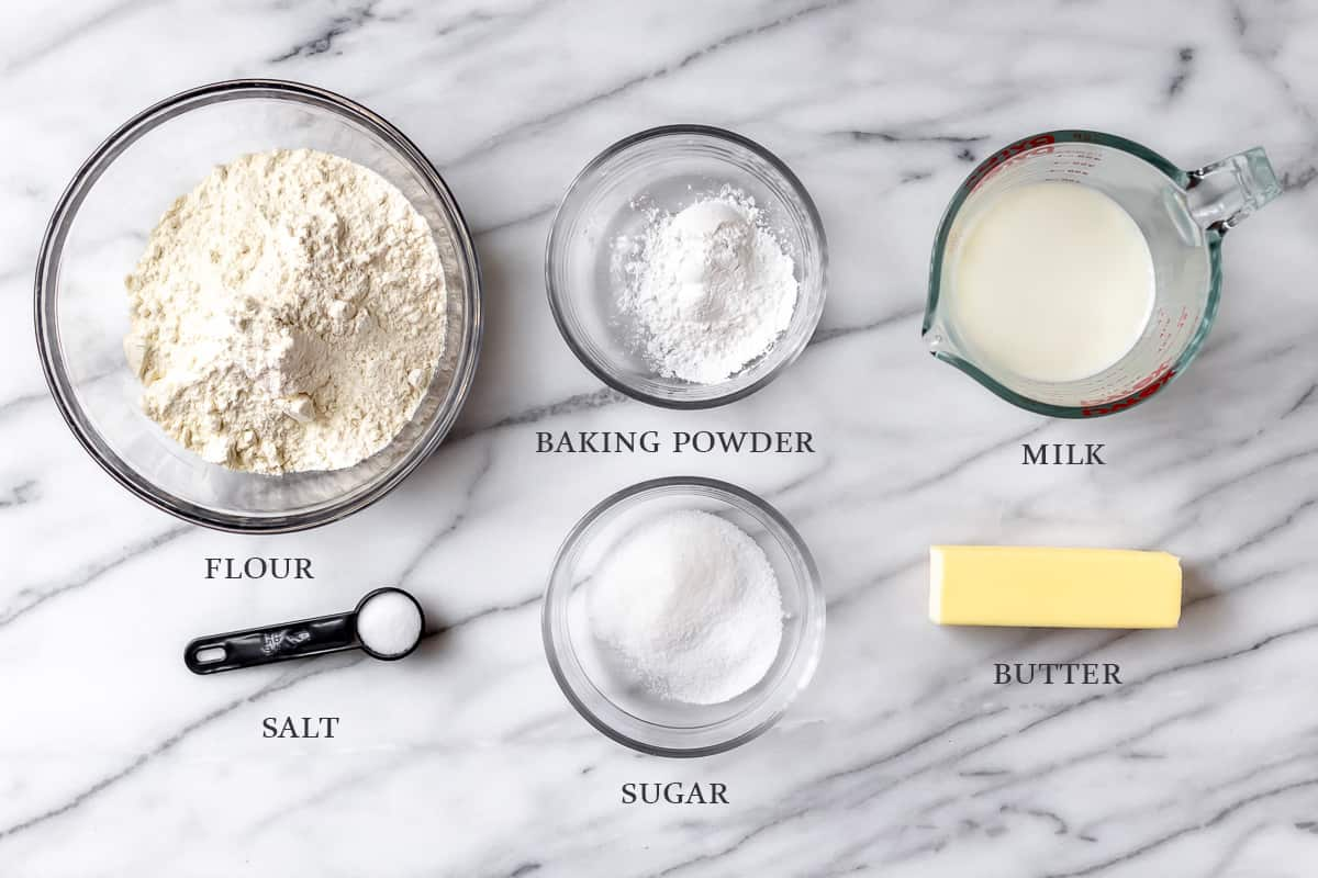 Ingredients needed to make homemade biscuits on a marble background with text overlay