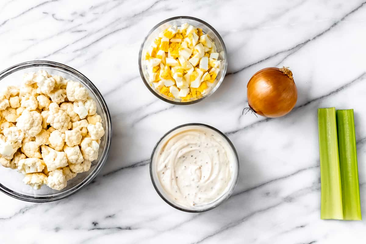 Cauliflower potato salad dressing in a small bowl with other ingredients around it