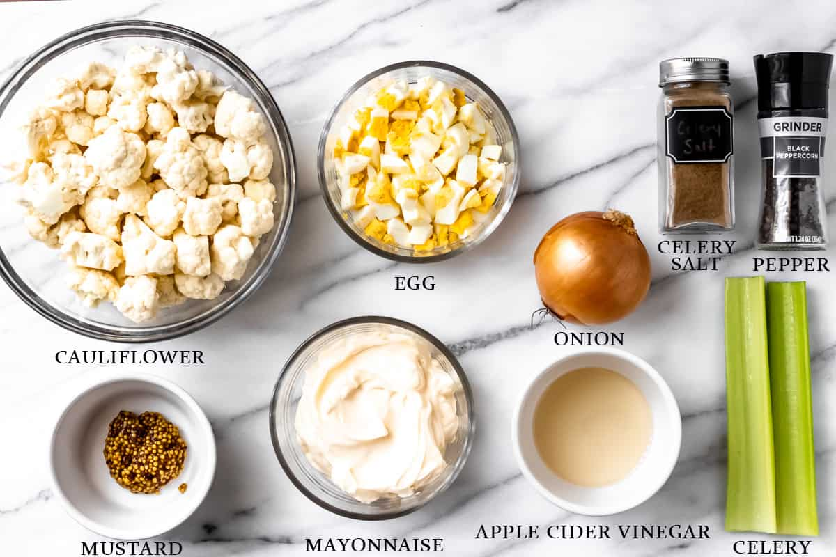 Ingredients to make keto potato salad on a marble background with labels