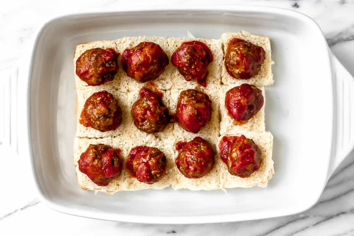 Slider rolls in a baking dish with a sauced meatball on each one
