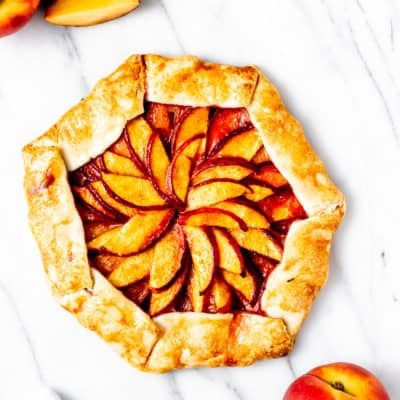Overhead of a peach galette with parts of whole peaches and peach slices showing on a marble backdrop