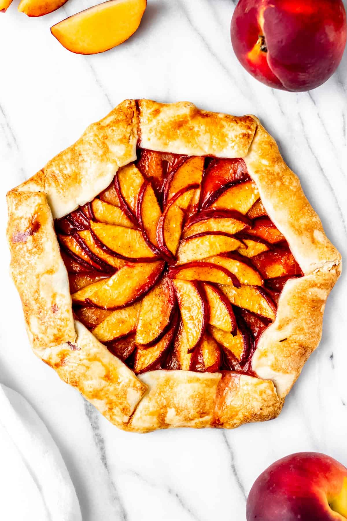 Overhead of a peach galette on a marble table with peaches and slices peaches around it