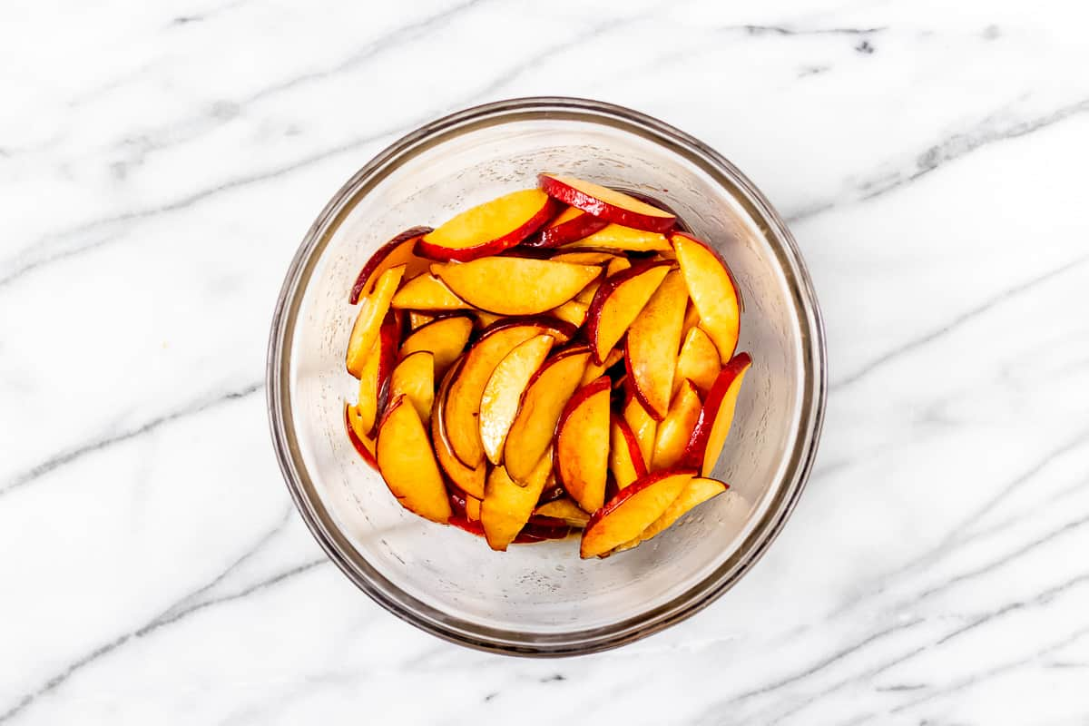A glass bowl of sliced peaches, brown sugar and cinnamon on a marble background