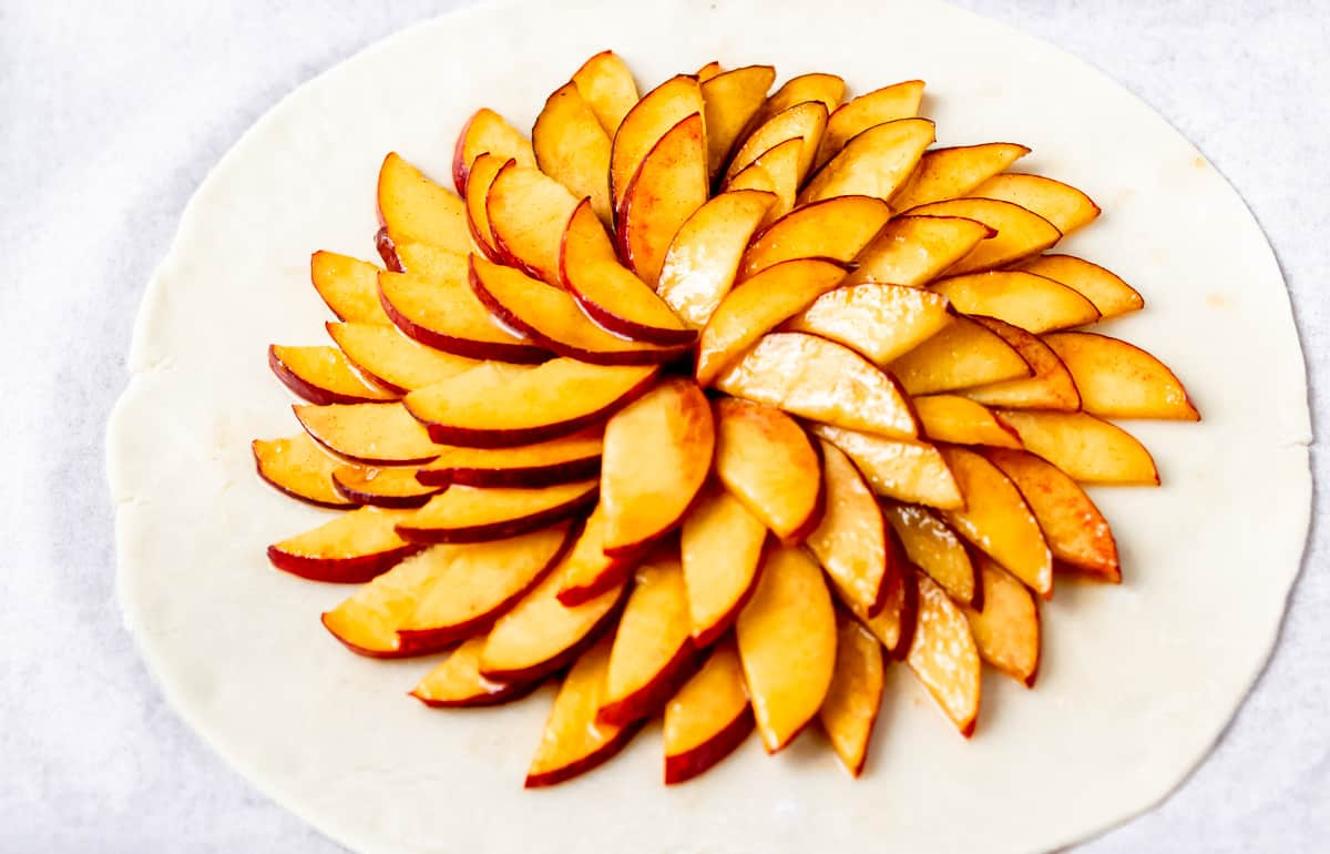 Pie crust with layered sliced peaches in the center