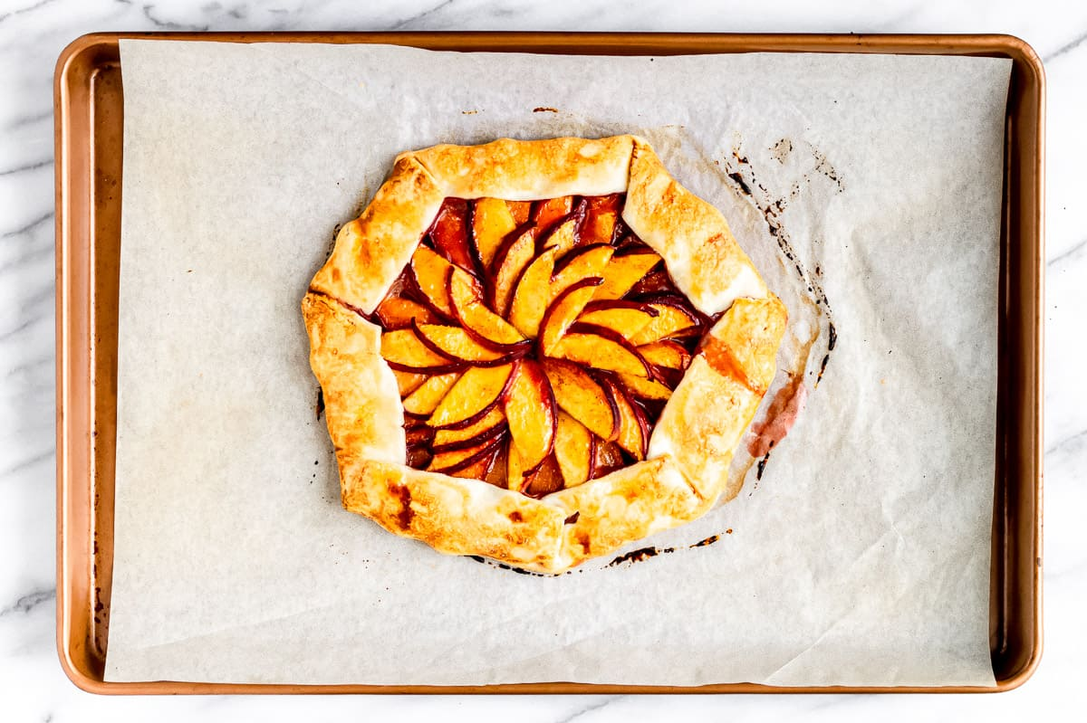 A baked peach galette on parchment paper