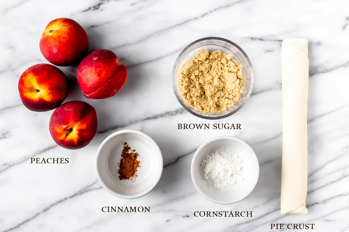 Ingredients to make a peach galette on a marble background with labels