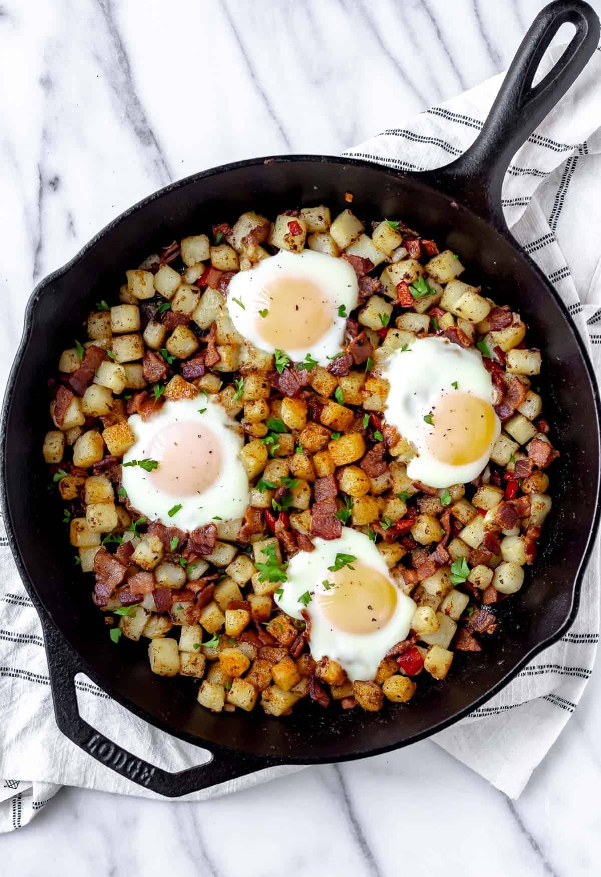 Potato hash with bacon and eggs in a cast iron skillet