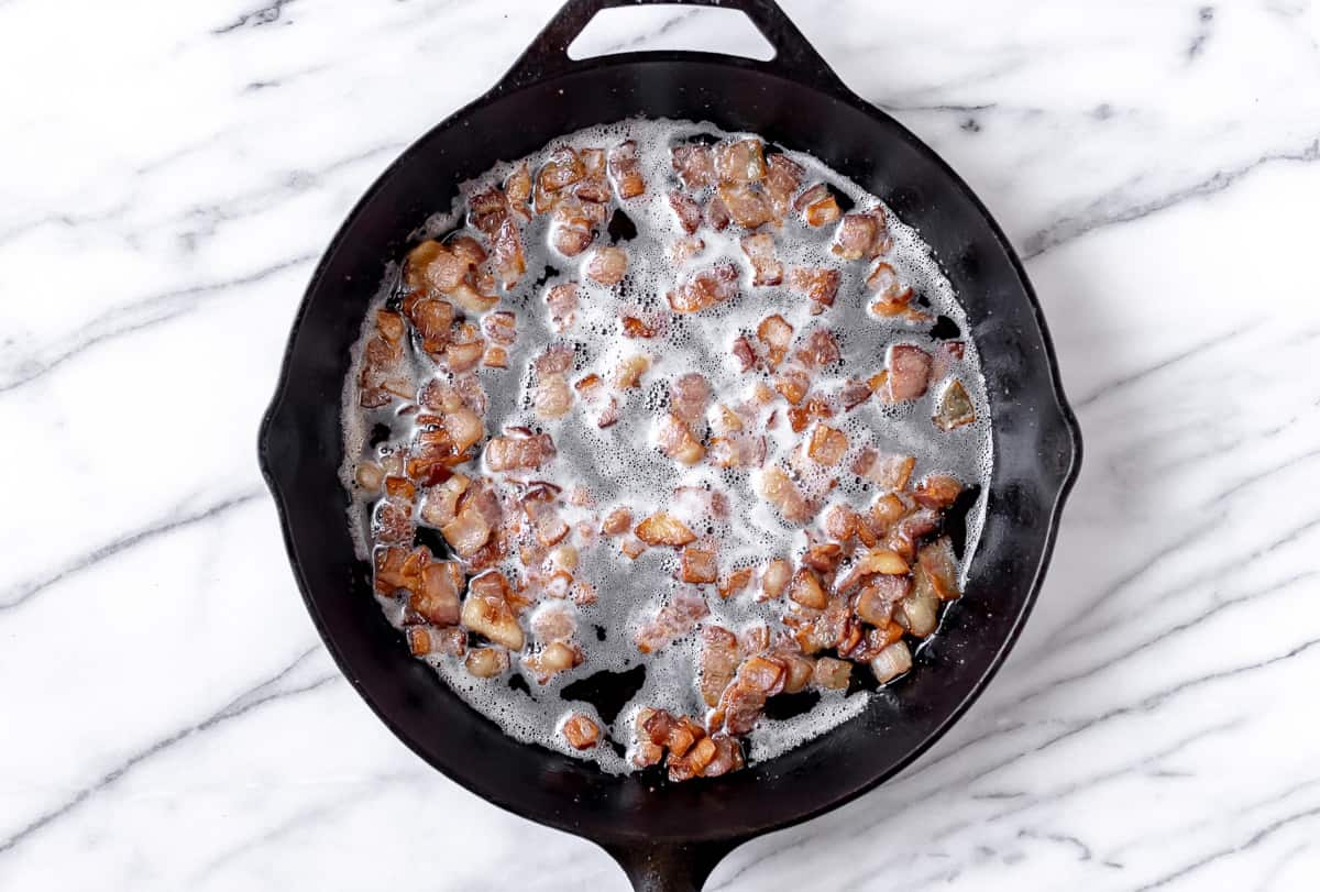 Diced bacon cooking in a cast iron skillet