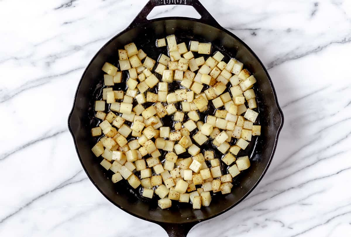 Diced potatoes cooking in a cast iron skillet