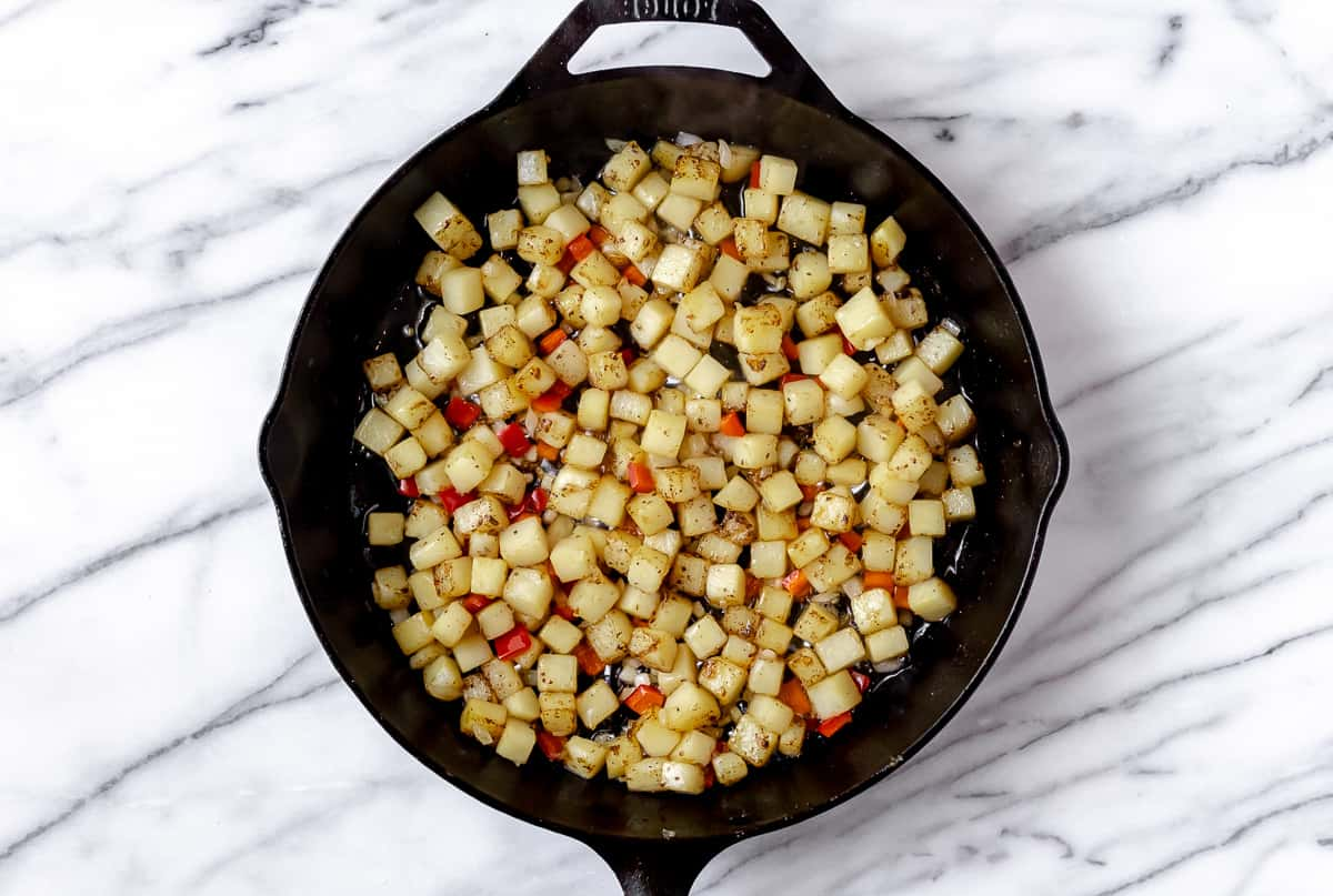 Diced potatoes, peppers and onion cooking in a cast iron skillet