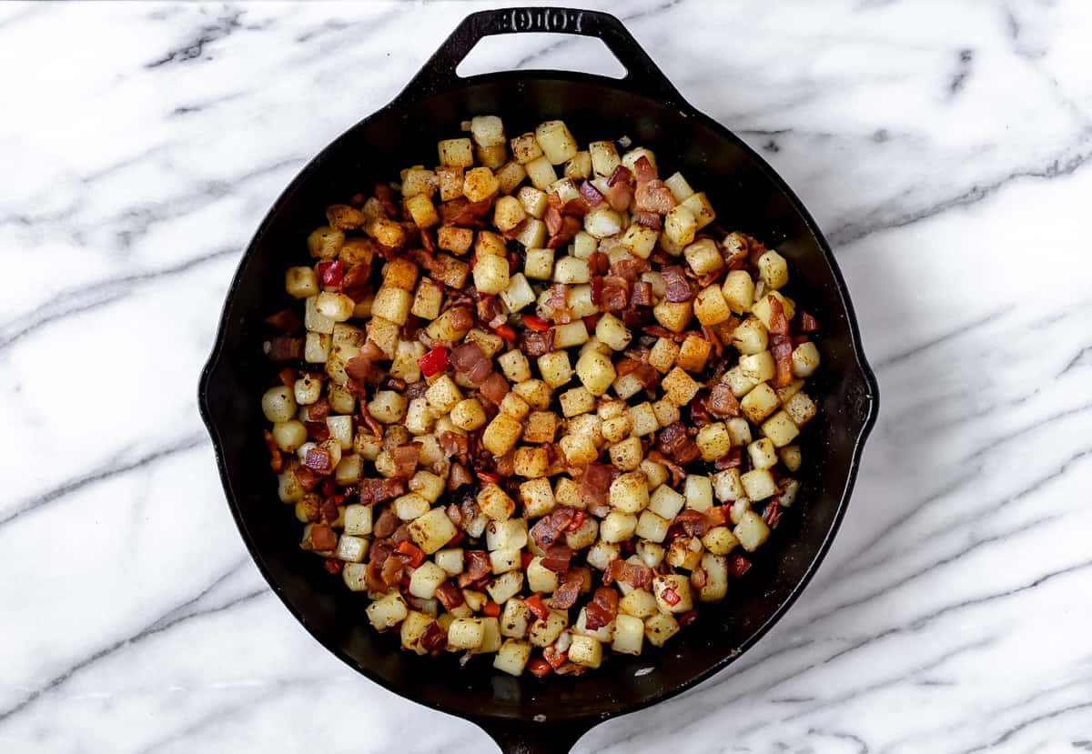 Diced potatoes, bacon, red pepper and onions in a cast iron skillet