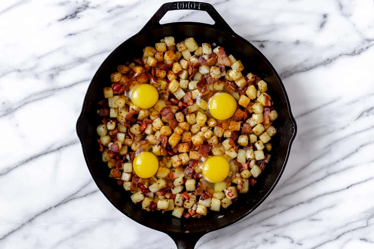 Potato hash with 4 eggs cracked into wells in a cast iron skillet before cooking the eggs