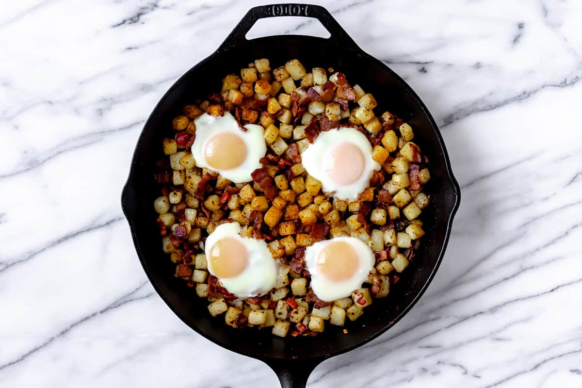 Breakfast hash with potatoes, bell pepper, onion, bacon and eggs in it