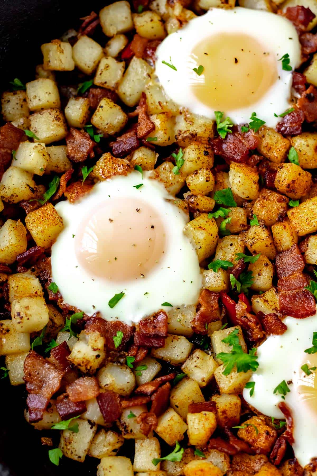 Close up of potato hash with over easy eggs, bacon, peppers and onions