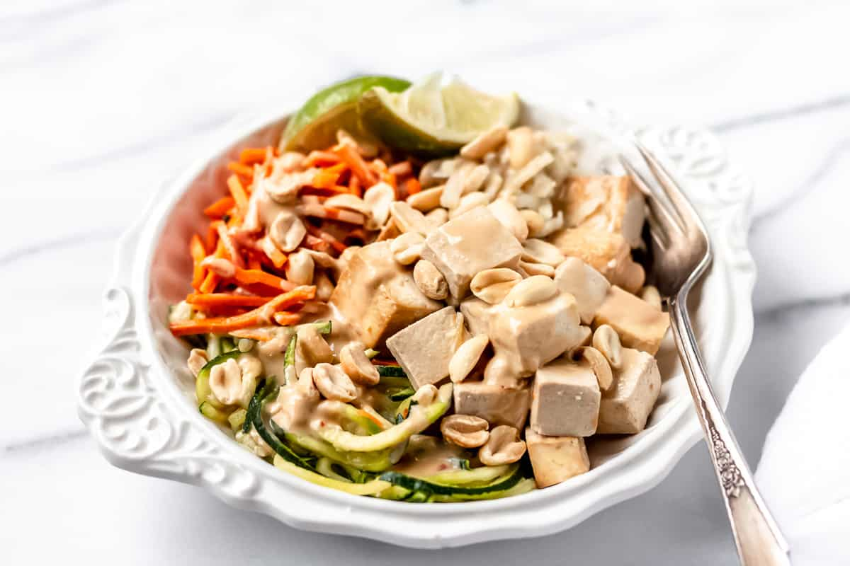 Sprinly Zucchini Noodle Pad Thai with Baked Tofu prepared and plated in a white bowl