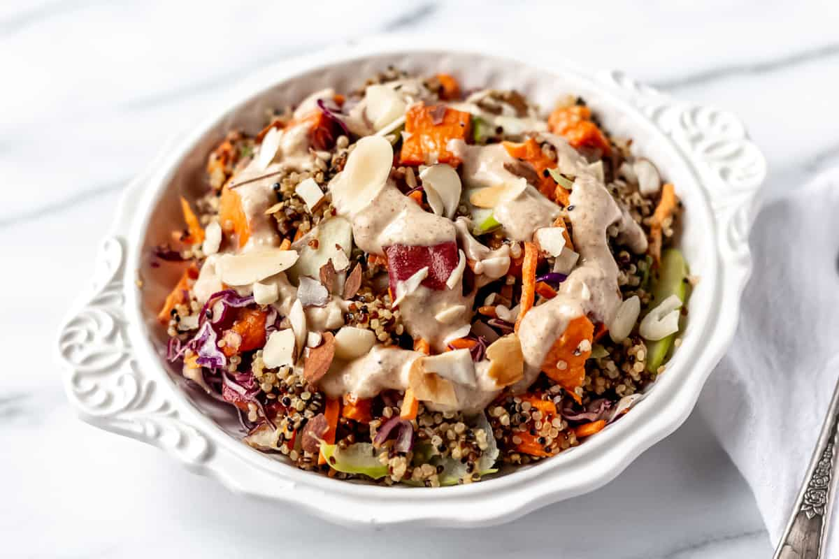 Sprinly Almond Ginger Quinoa Bowl with Roasted Sweet Potato and Sliced Apples prepared and plated in a white bowld