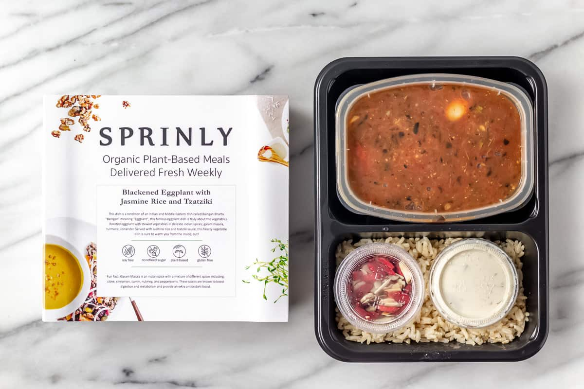 Sprinly Blackened Eggplant with Jasmine Rice and Tzatziki in package on a marble background