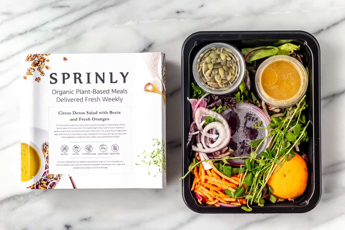 Citrus Detox Salad with Beets and Fresh Oranges from sprinly in packaging on a marble background