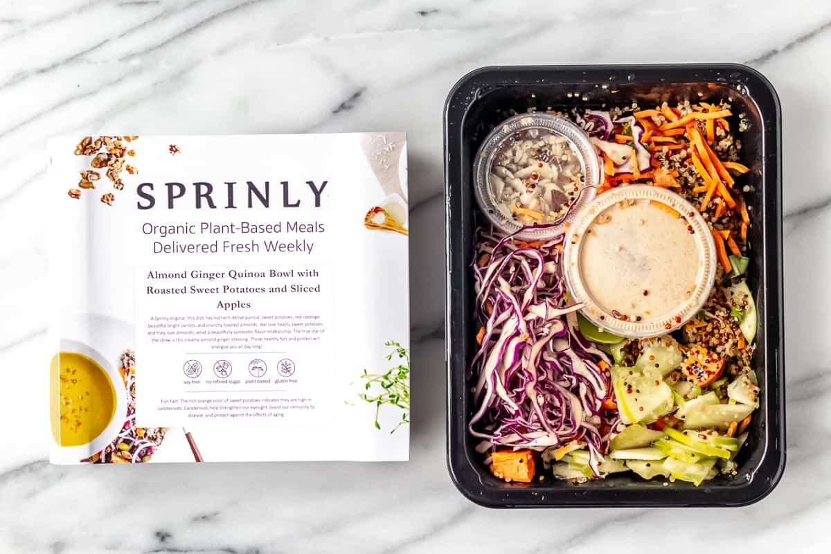 Almond Ginger Quinoa Bowl with Roasted Sweet Potato and Sliced Apples from sprinly in packaging on a marble background