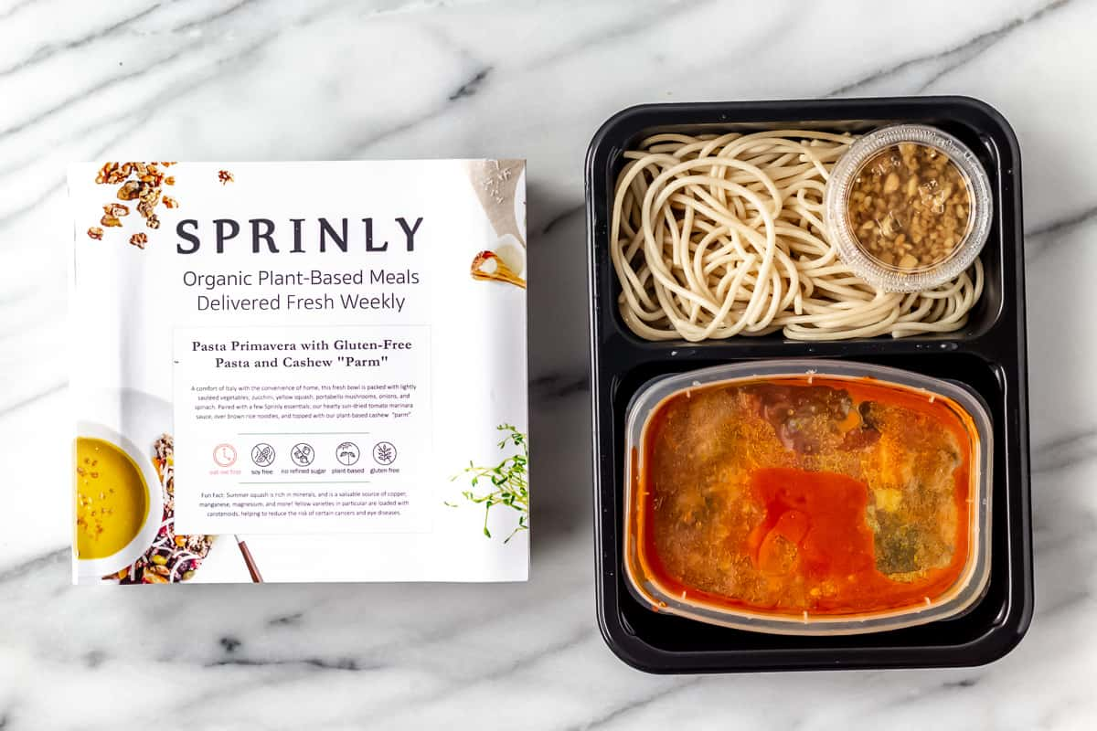 Pasta Primavera with Gluten Free Pasta and Cashew Parm from sprinly in package on a marble background