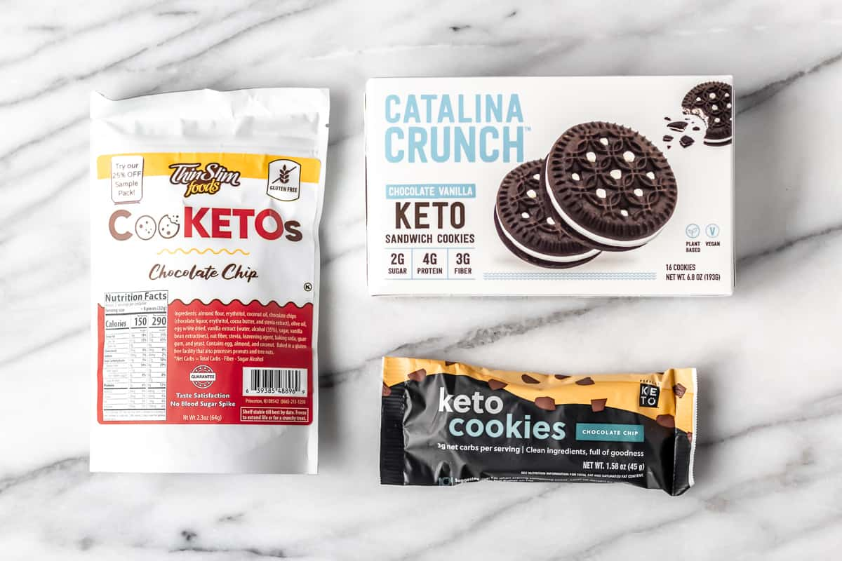 3 different brands of keto cookies on a marble background