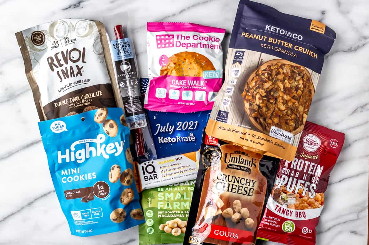 All of the keto snacks that comes in the July 2021 keto krate laid out on a marble background