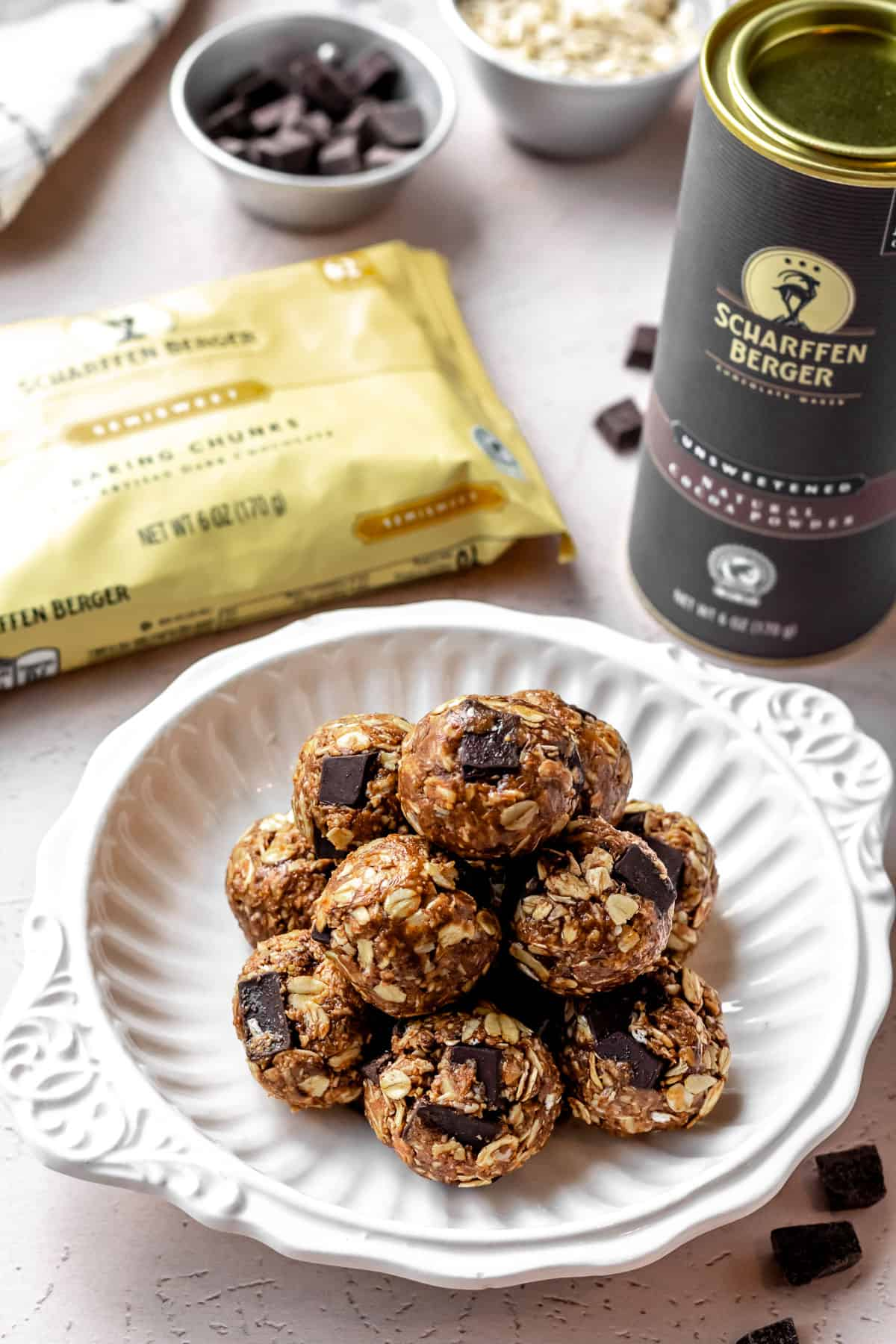 A white bowl of energy balls with a can of cocoa powder, a bag of chocolate chunks and bowls of ingredients in the background