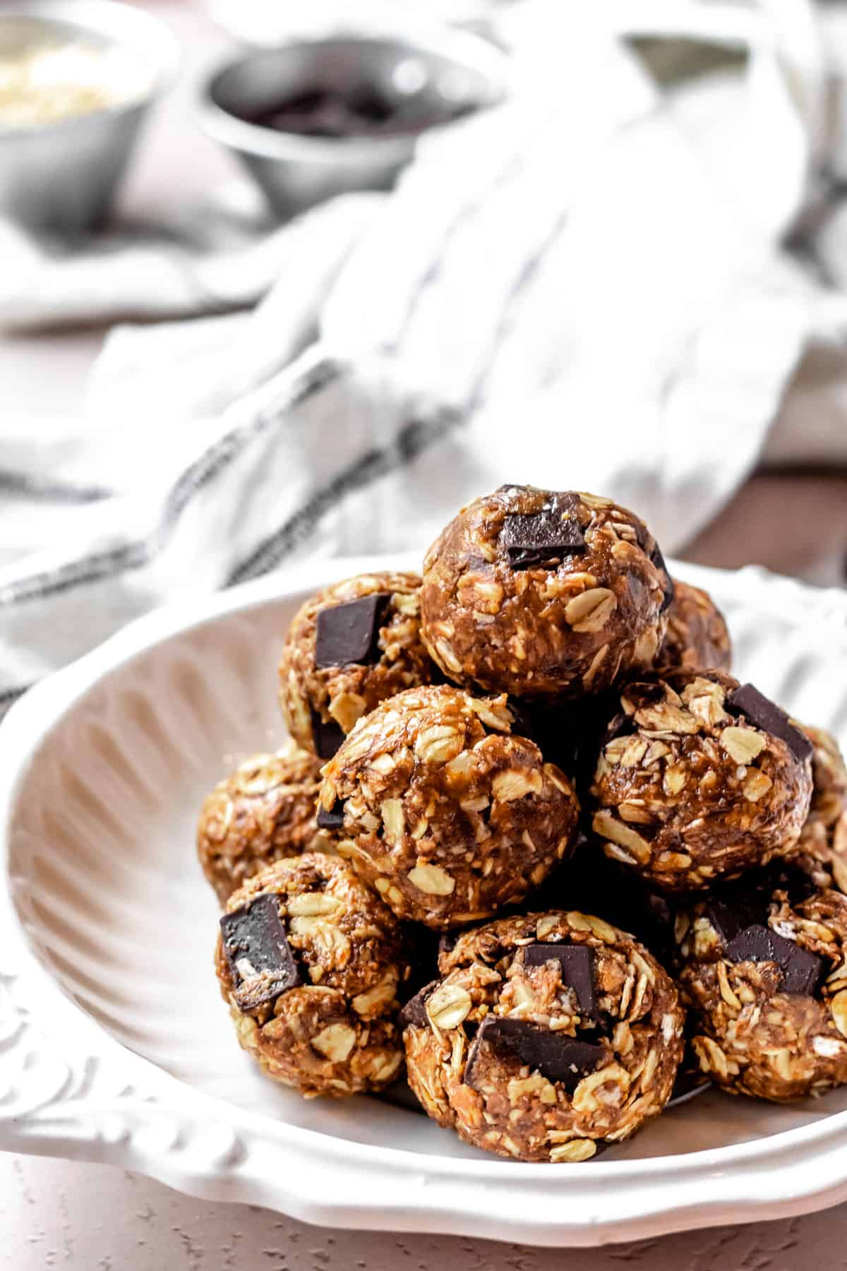 Close up of a stack of peanut butter energy balls with a towel and small bowls of ingredients in the background