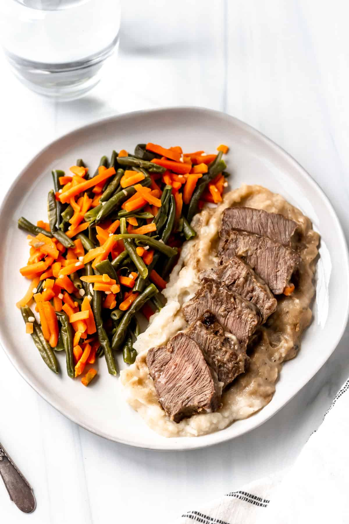 Freshly steak peppercorn, mashed potatoes, green beans and carrots on a white plate