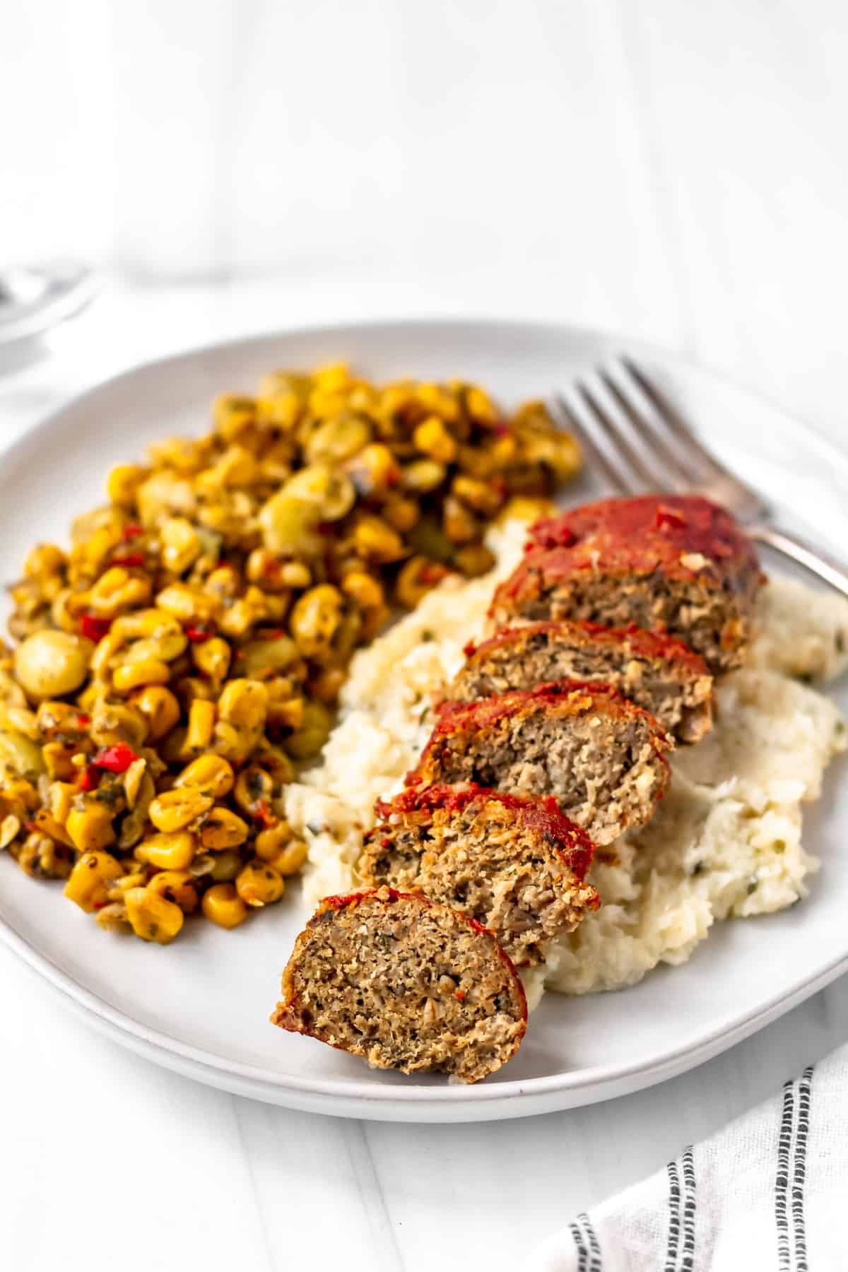 Freshly Down Home Meatloaf, potatoes and succotash on a white plate