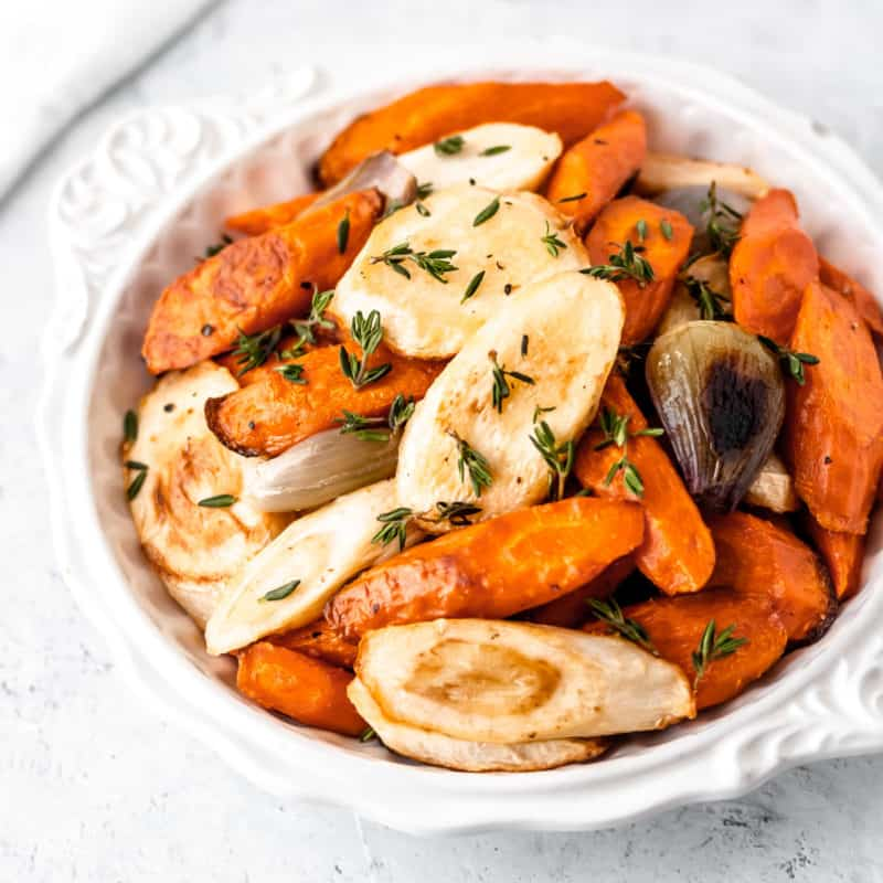 Close up of roasted carrots and parsnips in a white bowl.