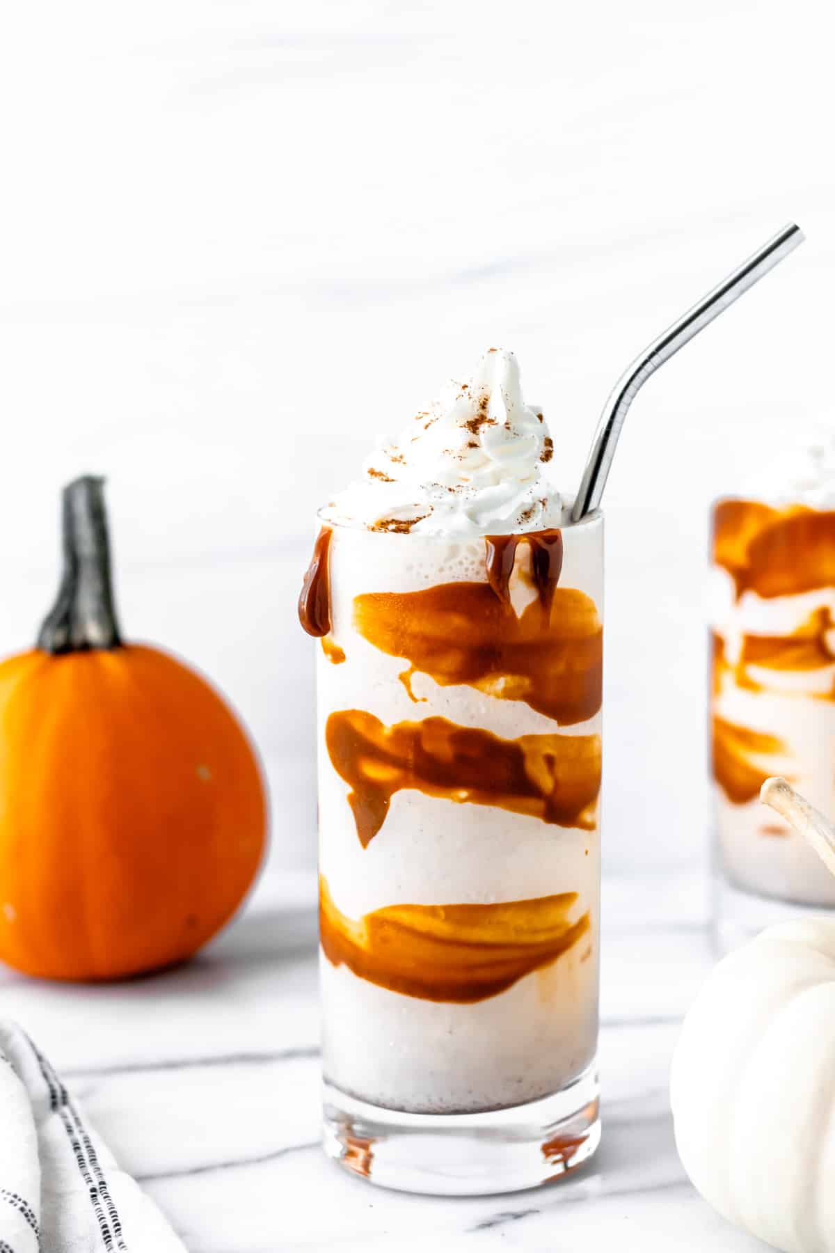 Pumpkin Spice Boozy Milkshake in a tall glass with a straw and pumpkins around it.