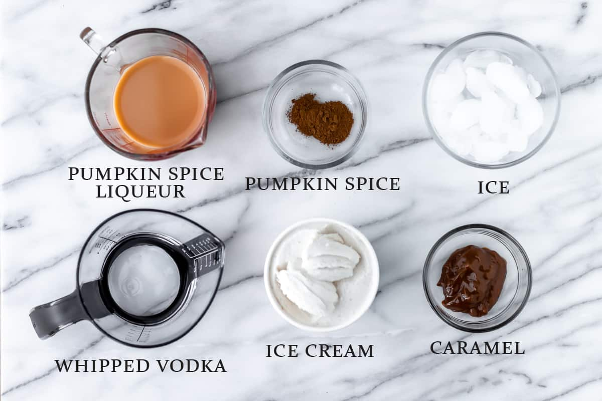 Ingredients to make a pumpkin spice boozy milkshake on a marble backdrop with text overlay.